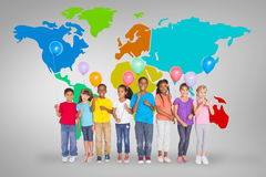 Composite image of elementary pupils holding balloons Stock Photo