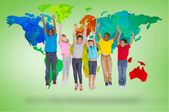 Composite image of elementary pupils jumping. Elementary pupils jumping against green vignette with world map Stock Photo