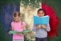 Composite image of elementary pupils reading Stock Photo
