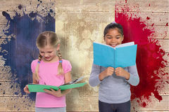 Composite image of elementary pupils reading Royalty Free Stock Image