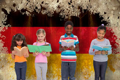 Composite image of elementary pupils reading Royalty Free Stock Photography