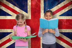 Composite image of elementary pupils reading Royalty Free Stock Photo