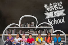 Composite image of elementary pupils reading books. Elementary pupils reading books against blackboard on wall Stock Photos