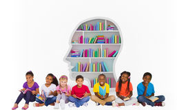 Composite image of elementary pupils reading books. Elementary pupils reading books against colorful books arranged in human face shape bookshelves Stock Photo