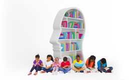 Composite image of elementary pupils reading books. Elementary pupils reading books against colorful books in human face shape bookshelves Royalty Free Stock Photos