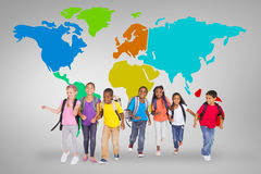 Composite image of elementary pupils running. Elementary pupils running against grey vignette with world map Royalty Free Stock Images