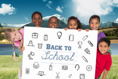 Composite image of elementary pupils showing card Royalty Free Stock Photo