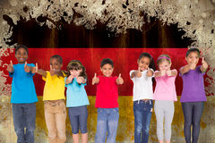 Composite image of elementary pupils smiling showing thumbs up Stock Image