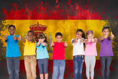 Composite image of elementary pupils smiling showing thumbs up Stock Images