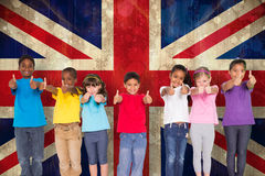 Composite image of elementary pupils smiling showing thumbs up Royalty Free Stock Image