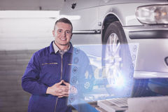 Composite image of engineering interface. Engineering interface against front view of a mechanic next to a car Royalty Free Stock Photography