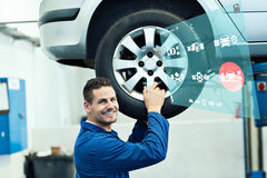 Composite image of engineering interface. Engineering interface against mechanic adjusting the tire wheel Royalty Free Stock Images