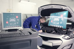 Composite image of engineering interface. Engineering interface against mechanic examining an engine of a car Royalty Free Stock Photo