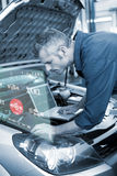 Composite image of engineering interface. Engineering interface against mechanic using laptop on car Royalty Free Stock Photo