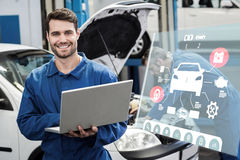 Composite image of engineering interface. Engineering interface against smiling mechanic using a laptop Stock Photo