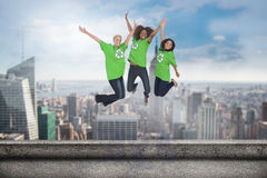 Composite image of enviromental activists jumping and smiling Stock Image
