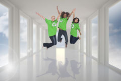 Composite image of enviromental activists jumping and smiling Royalty Free Stock Images