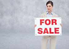 Composite image of estate agent holding for sale sign Royalty Free Stock Photo