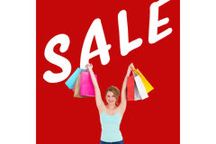Composite image of excited blonde holding up shopping bags Royalty Free Stock Image