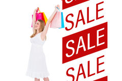 Composite image of excited blonde holding up shopping bags in white dress Royalty Free Stock Photography