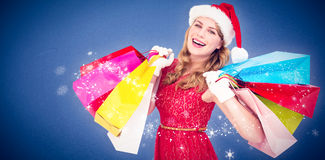 Composite image of excited blonde in santa hat holding shopping bags Stock Photos