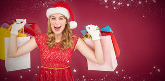 Composite image of excited blonde in santa hat holding shopping bags Stock Image