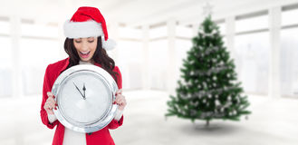 Composite image of excited brunette holding a clock. Excited brunette holding a clock against home with christmas tree Stock Image