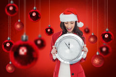 Composite image of excited brunette holding a clock. Excited brunette holding a clock against red snowflake background Stock Photography