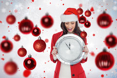Composite image of excited brunette holding a clock. Excited brunette holding a clock against snowflake pattern Royalty Free Stock Photos