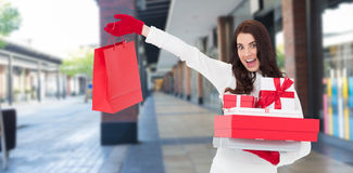 Composite image of excited brunette holding gifts and showing shopping bag Stock Image