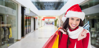 Composite image of excited brunette holding shopping bags and credit card. Excited brunette holding shopping bags and credit card  against interior of modern Royalty Free Stock Photos