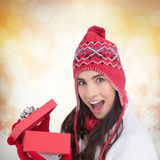 Composite image of excited brunette opening a christmas gift. Excited brunette opening a christmas gift against glowing christmas background Royalty Free Stock Photo