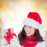 Composite image of excited brunette in santa hat showing gift. Excited brunette in santa hat showing gift against glowing christmas background Royalty Free Stock Image