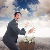 Composite image of excited businessman catching Stock Photo