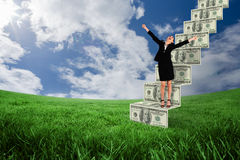 Composite image of excited businesswoman cheering. Excited businesswoman cheering against green field under blue sky Stock Image