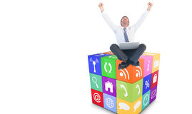 Composite image of excited cheering businessman sitting using his laptop Royalty Free Stock Photography
