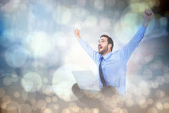 Composite image of excited cheering businessman sitting using his laptop Stock Image