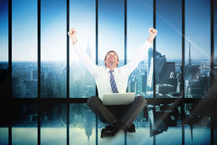 Composite image of excited cheering businessman sitting using his laptop Stock Photo