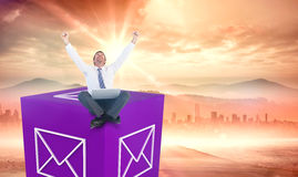 Composite image of excited cheering businessman sitting using his laptop Royalty Free Stock Photo