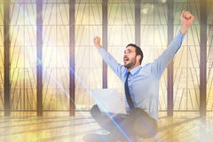Composite image of excited cheering businessman sitting using his laptop Royalty Free Stock Image