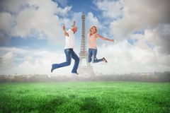 Composite image of excited couple cheering and jumping Royalty Free Stock Photo