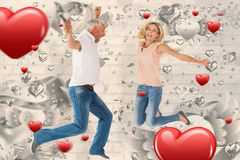 Composite image of excited couple cheering and jumping Stock Image