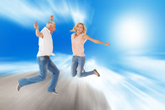 Composite image of excited couple cheering and jumping Stock Photography