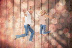 Composite image of excited couple cheering and jumping Stock Photos