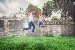 Composite image of excited couple cheering and jumping Royalty Free Stock Image