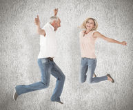 Composite image of excited couple cheering and jumping Stock Photo