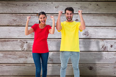 Composite image of excited couple cheering in red and yellow tshirts Stock Images