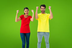 Composite image of excited couple cheering in red and yellow tshirts Royalty Free Stock Photography