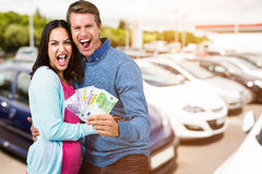 Composite image of excited couple holding money Royalty Free Stock Image