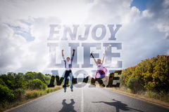 Composite image of excited couple jumping on the road Stock Photo